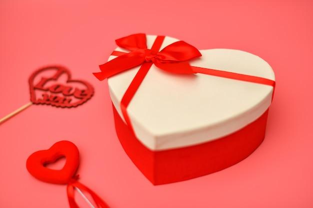 Размытая подарочная коробка на день святого валентина в форме сердца с красной лентой на розовом