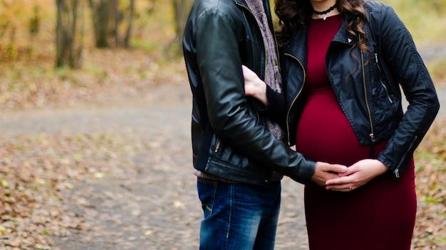 秋の森で妊娠中の女性を抱きしめる男、
