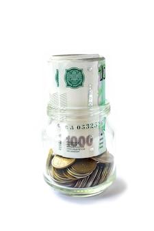 Деньги монеты в стеклянной банке.