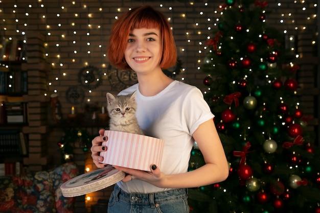 白人の外観の魅力的な女の子は、小さな子猫の入った箱を手に持っています。