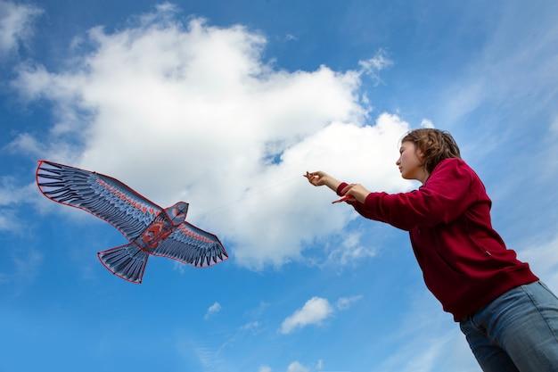 Девушка запускает воздушный змей. летающих змей. воздушный змей в форме орла. голубое небо с облаками.