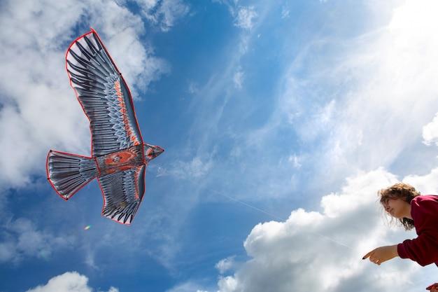 Девушка запускает воздушный змей. летающих змей. голубое небо с облаками. воздушный змей в форме орла.