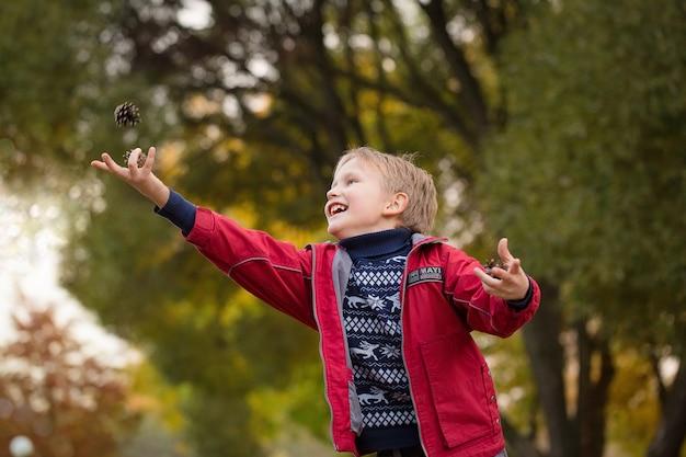 ジャケットを着た少年は公園でバンプを投げます。ヨーロッパの外観の子供の肖像画。明るい感情。