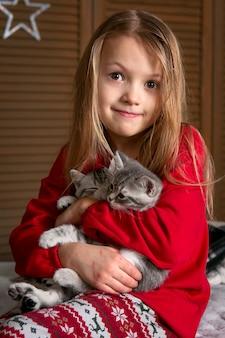 赤いパジャマの女の子がかわいい子猫と一緒にベッドに座っています。明るい感情。