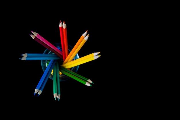 Разноцветные карандаши на черном фоне в форме сердца, место для надписи.