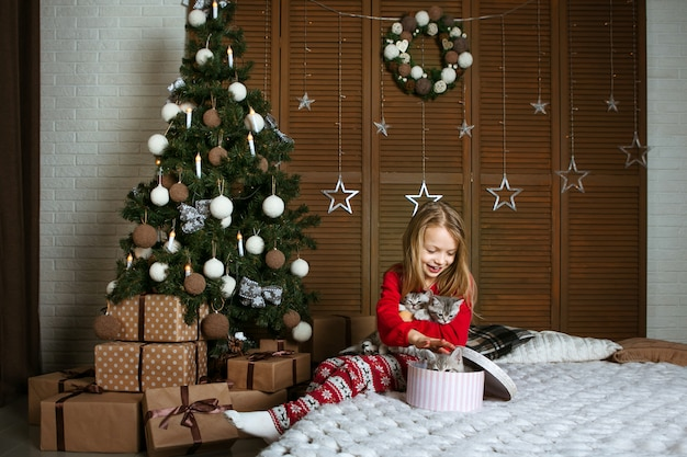 Девушка в красной пижаме сидит на кровати с милыми котятами. яркие эмоции. подарки под елку.