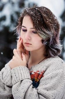 Женщина кавказской внешности в свитере. снежный зимний день. задумчивая молодая женщина.