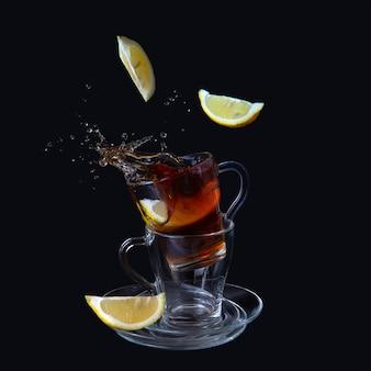 Прозрачные чашки с чаем. ломтики лимона попадают в чашку. всплески, брызги.