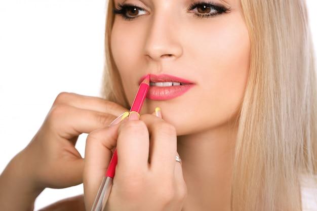 Косметолог делает перманентный макияж на губах женщины