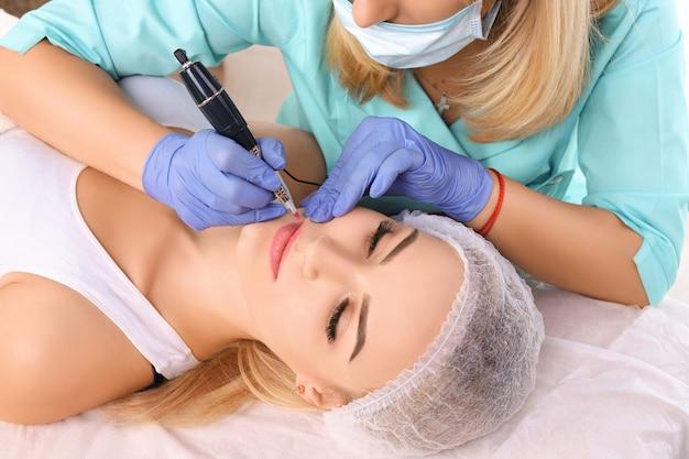 女性の唇に恒久的な化粧をする美容師