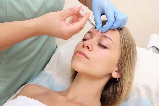 Красивая женщина получает укол в лицо.