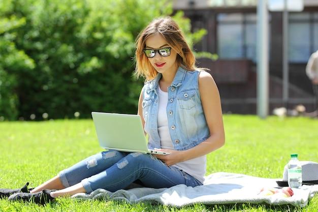 ノートパソコンで草の上に座っている若い女の子