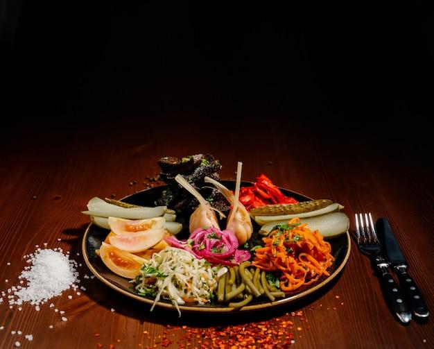 Разные виды овощей на черной плите.