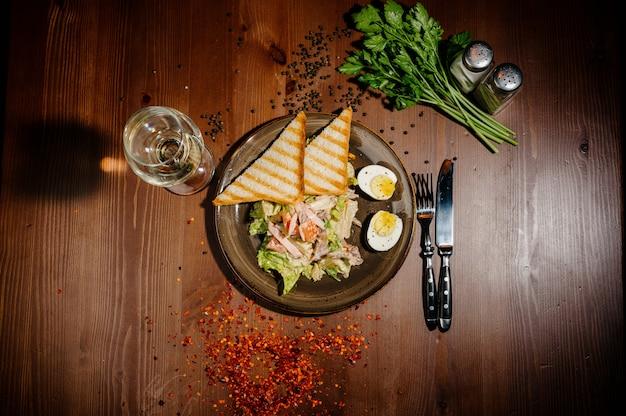 木製テーブルの上の黒い皿にシーザーサラダ。トップビュー