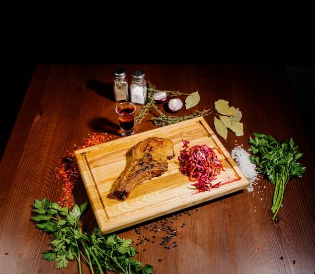 揚げ肉のジューシーな部分は、木製のテーブルに対してまな板の上にあります。