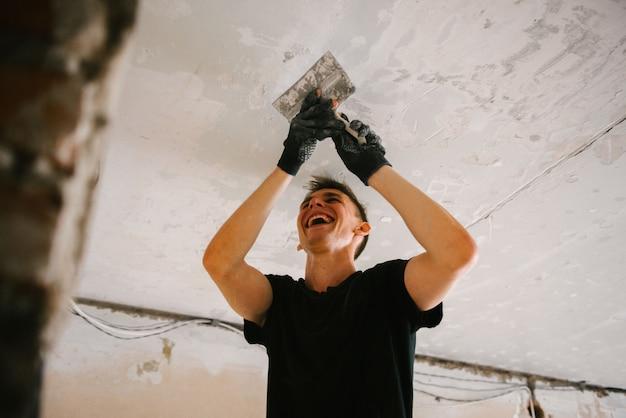 ヘラで天井から古いペンキを取り除く男性