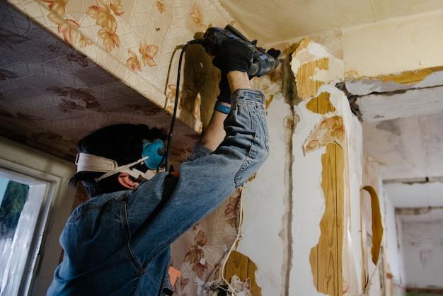 Рабочий сверлит стену с помощью перфоратора. ремонт в квартире