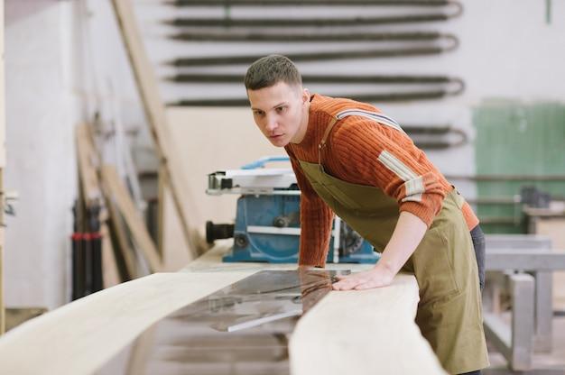 Мастер работает на плоскошлифовальном станке в столярной мастерской