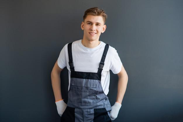 Портрет молодой, улыбающийся, профессиональный работник в сером комбинезоне и белой футболке, стоя на сером фоне.