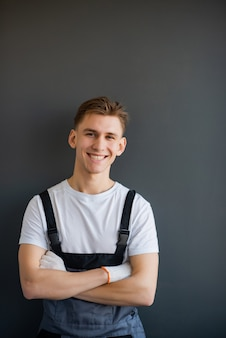 Портрет молодого, улыбающегося, профессионального работника в сером комбинезоне и белой футболке, стоя со скрещенными руками на сером фоне.