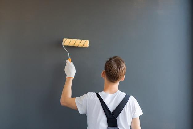 労働者は彼の背中に立って、灰色の背景に壁を塗る