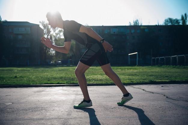 Спортсмен на стадионе стоит на стартовой дорожке для бега