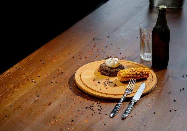 まな板とスレートのテーブルにスパイスとハーブのおいしい牛肉のハンバーガーステーキ。木製のまな板にジューシーな揚げ肉のカツレツ