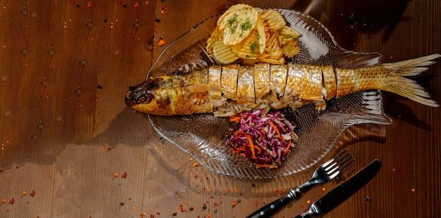 Рыбное блюдо - жареное филе рыбы с овощами на темном деревянном столе. вид сверху