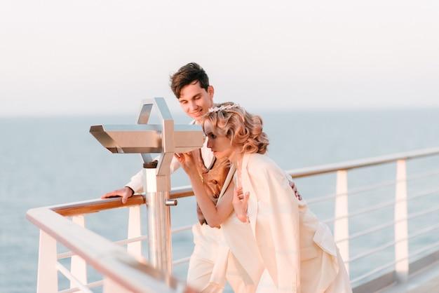 海のクルーズ客船のデッキの上の若い美しいカップル