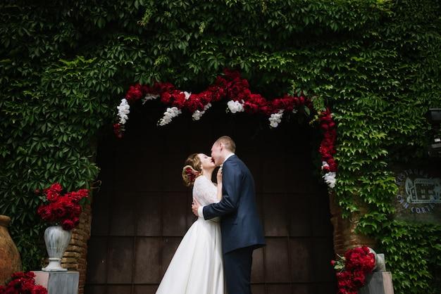 スーツを着た新郎とウェディングドレスを着た花嫁が結婚式で結婚式のアーチに立っています。