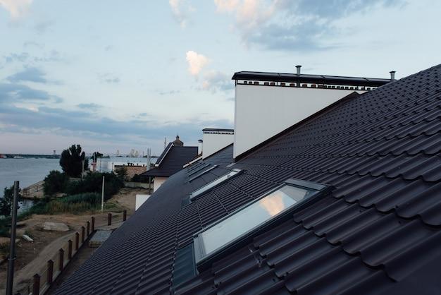 Черепичная крыша двухэтажного белого коттеджа