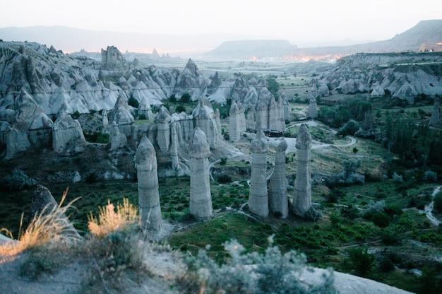 Скалы, похожие на грибы, ярко освещенные закатом в каппадокии, турция