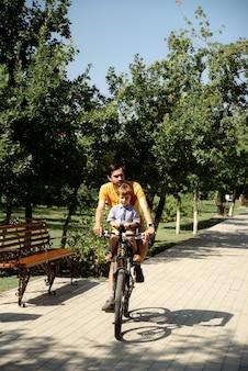 父は息子と公園のチャイルドシートに自転車に乗る