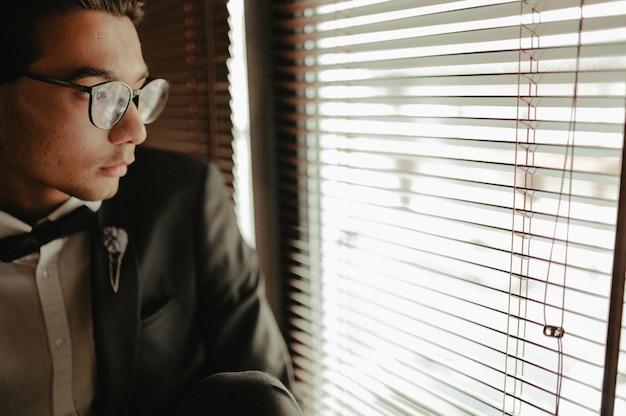 Молодой человек в торжественная одежда и галстук-бабочка, глядя в сторону, сидя в кресле в интерьере чердак