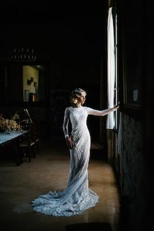 Невеста в белом свадебном платье позирует в помещении