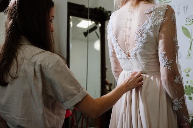 ブライダル衣料品店で最終的なタッチを作る洋裁を持つ女性