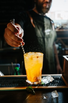 甘くて新鮮なオレンジ色の夏のカクテルをグラスでかき混ぜるバーテンダー