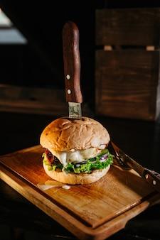 Большой сочный бургер на разделочной доске
