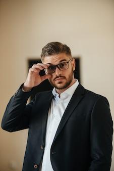 黒いスーツと白いシャツを着た男性が、男性の服を宣伝するために屋内でポーズをとります。紳士服店の撮影