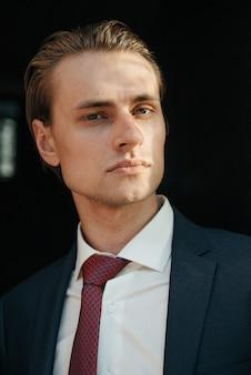 黒のスーツと赤いネクタイの男性モデルは、紳士服の広告のためにポーズします。紳士服店の撮影