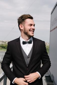 黒いスーツを着た男が上着を締めます。紳士服の広告。