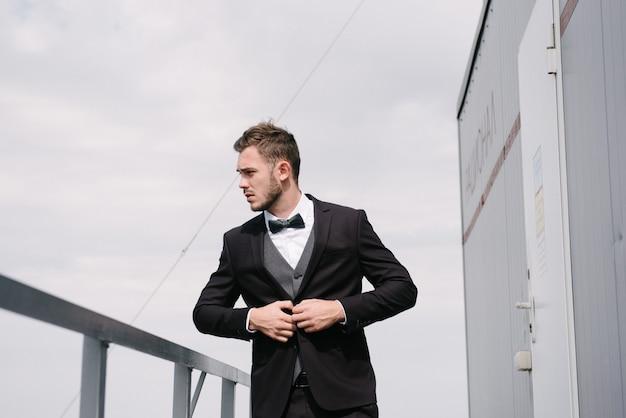 黒いスーツを着た男が上着を締めます。