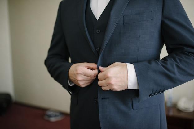 男が黒いジャケットを着ています。男がベストを着ています。