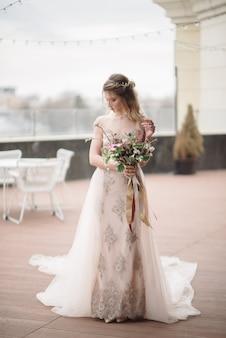 Молодая женщина позирует в белом свадебном платье