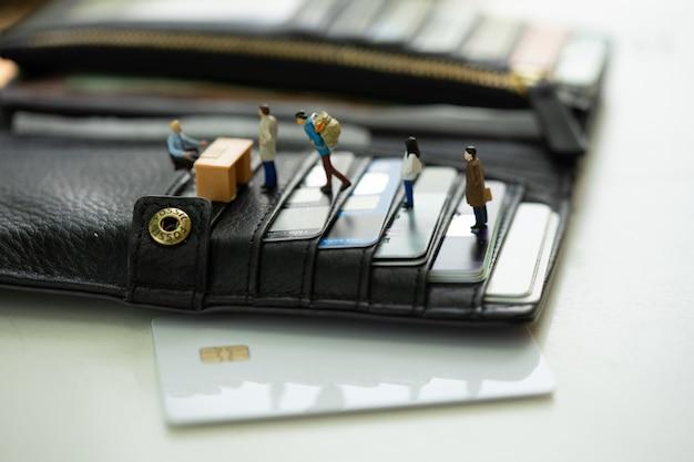 クレジットカードで満たされた財布の銀行カウンターで並んでいるミニチュアの人々。