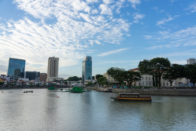 Городской пейзаж и чартер лодки на набережной вдоль реки сингапур.