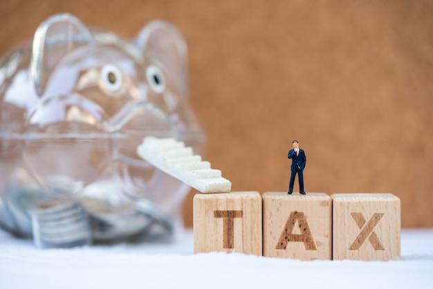 Блок слова налог с копилкой. доходы, расходы, налоги и финансовые данные.