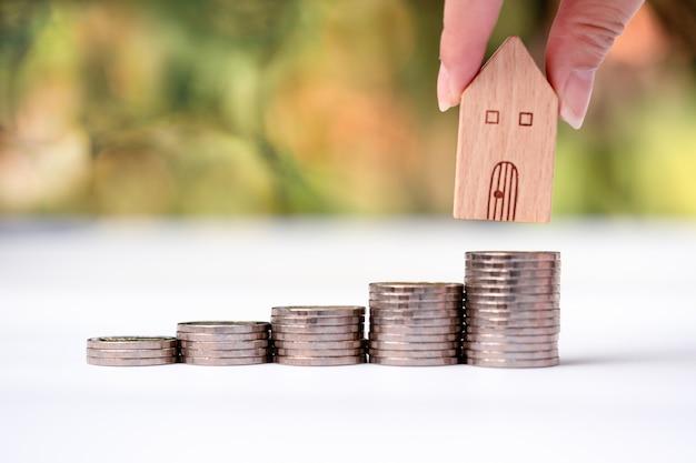 Рука женщины кладя модель дома на стог монеток.