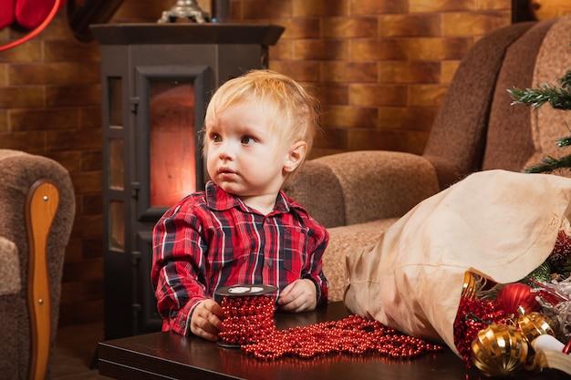1 살짜리 아이가 빨간 구슬로 크리스마스 트리를 장식하는 것을 돕습니다.