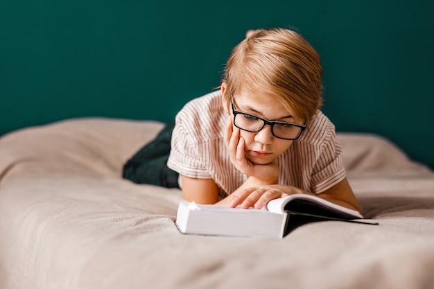 안경을 쓴 10 살 소년이 침대에 누워 큰 책을 읽고 있습니다.